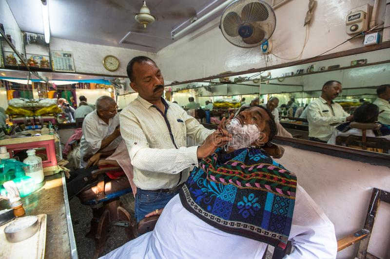 Hairdresser cuts hair of the pilgrim. VARANASI, INDIA - MAR 16, 2018: Hairdresser cuts hair of the pilgrim. A haircut in Varanasi is considered to be a kind of royalty free stock photos