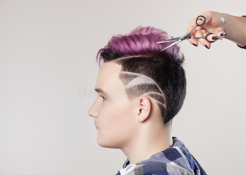 Hairdresser cuts hair. Portrait of a beautiful young teenager with a beautiful creative hairstyle royalty free stock image