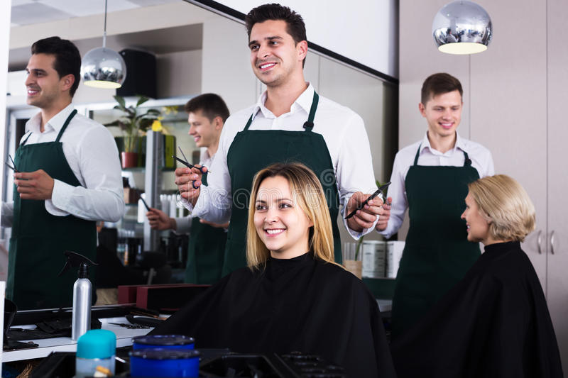 Hairdresser cuts hair at salon. Positive hairdresser cuts hair of blonde girl at salon stock photo