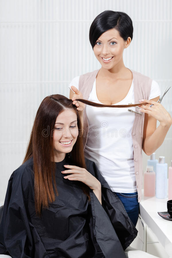 Hairdresser cuts hair of woman in hairdress salon royalty free stock photography