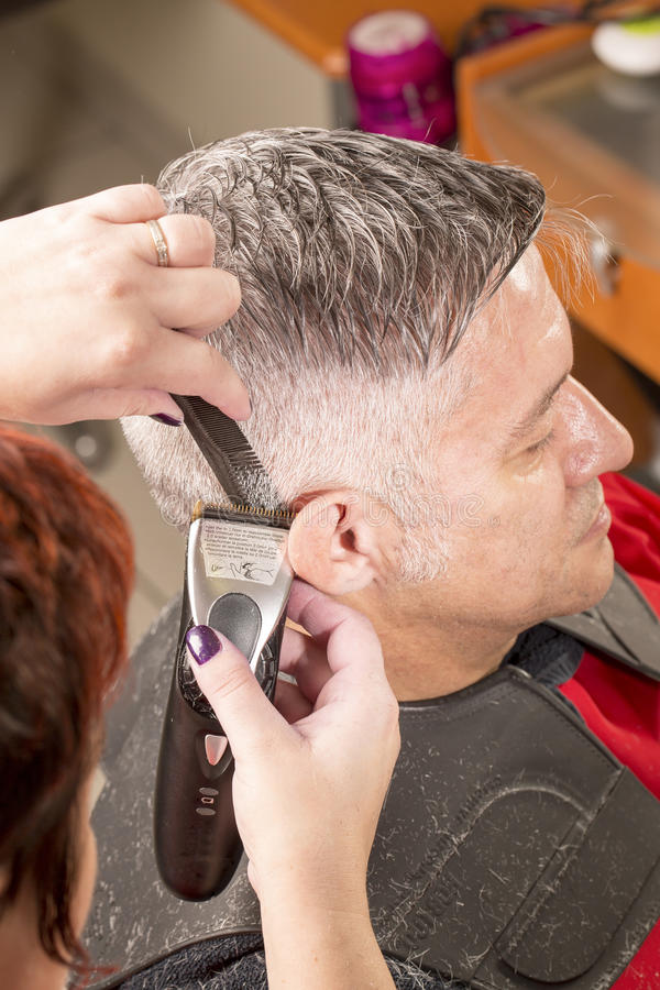 Hairdresser cuts hair royalty free stock photography