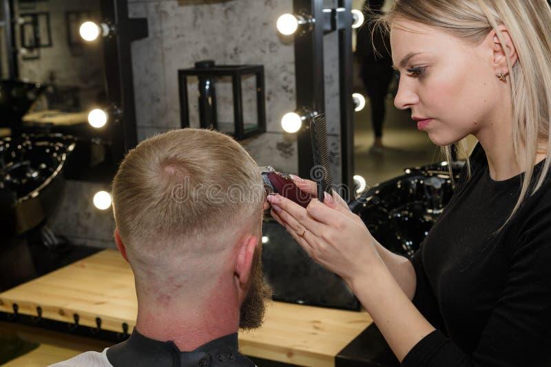 Hairdresser cuts machine man closeup in a barbershop stock image
