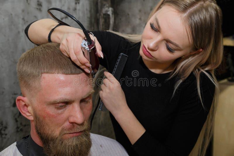 Hairdresser cuts machine man closeup in a barbershop stock images
