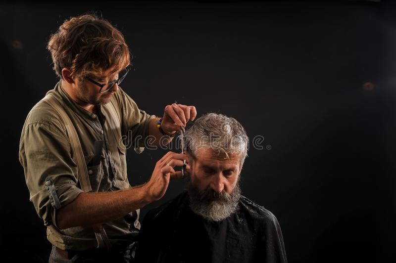Hairdresser cuts senior citizen with a beard on a dark background royalty free stock photo