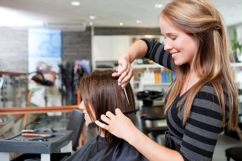 Hairdresser Cutting Client's Hair. In beauty salon royalty free stock photo