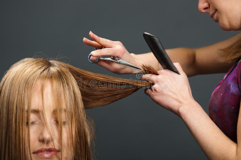 Hairdresser cutting customer's hair stock photos