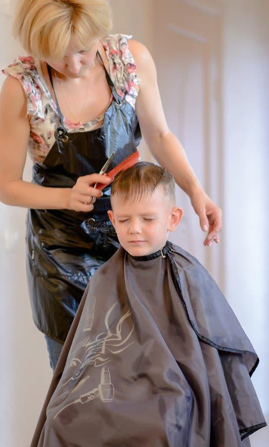 Hairdresser cutting a little boys hair stock image