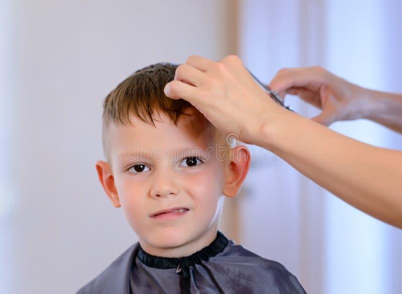 Hairdresser cutting a little boys hair royalty free stock photo