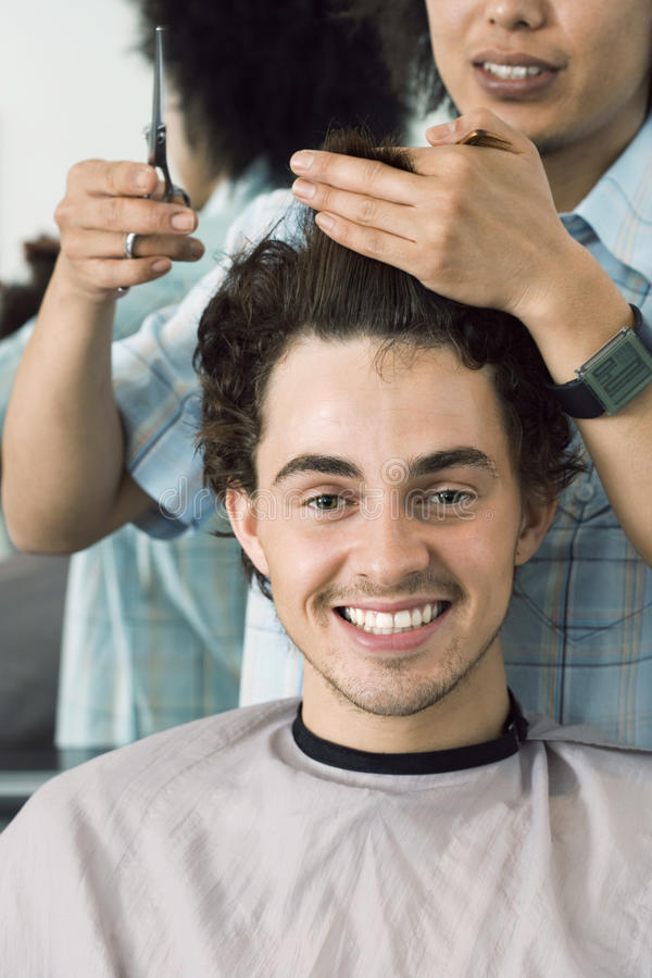Hairdresser cutting man's hair in barbers shop, smiling, front view, close-up, portrait stock photos