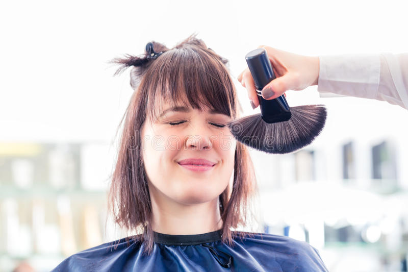 Hairdresser cutting woman hair in shop royalty free stock photography