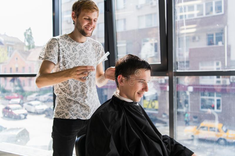 Hairdresser does hair with comb of handsome satisfied client in professional hairdressing salon royalty free stock images