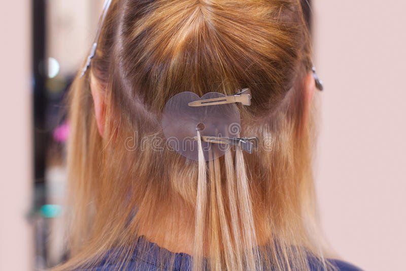 The hairdresser does hair extensions to a young girl, a blonde in a beauty salon. stock photo