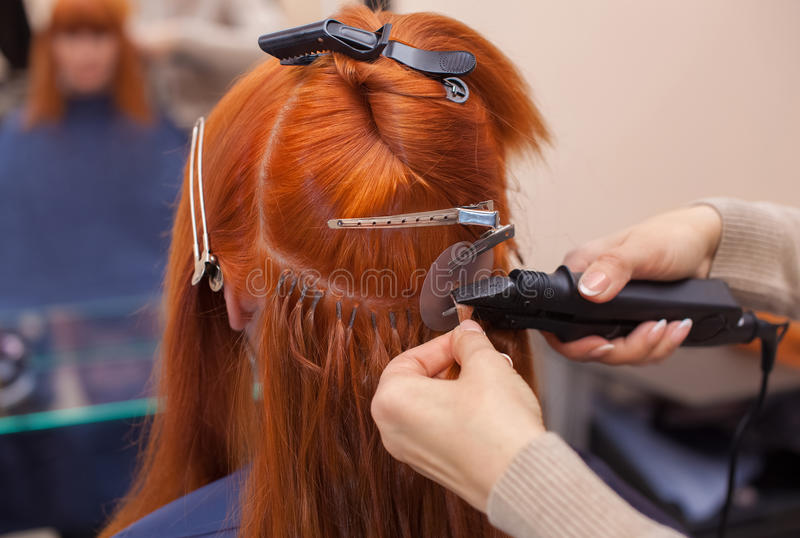 The hairdresser does hair extensions to a young, red-haired girl, in a beauty salon. Professional hair care royalty free stock photo