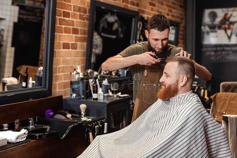 Barber and bearded man in barber shop stock photos