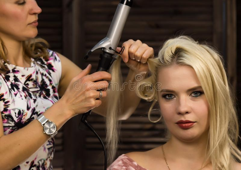 Hairdresser does hairstyle for luxurious blond woman. coiffure in the form of big curl. Concept wedding hairstyle royalty free stock photography
