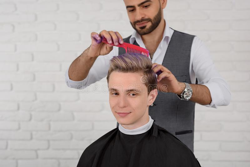 Hairdresser doing hair violet colored toning for young boy. royalty free stock photos
