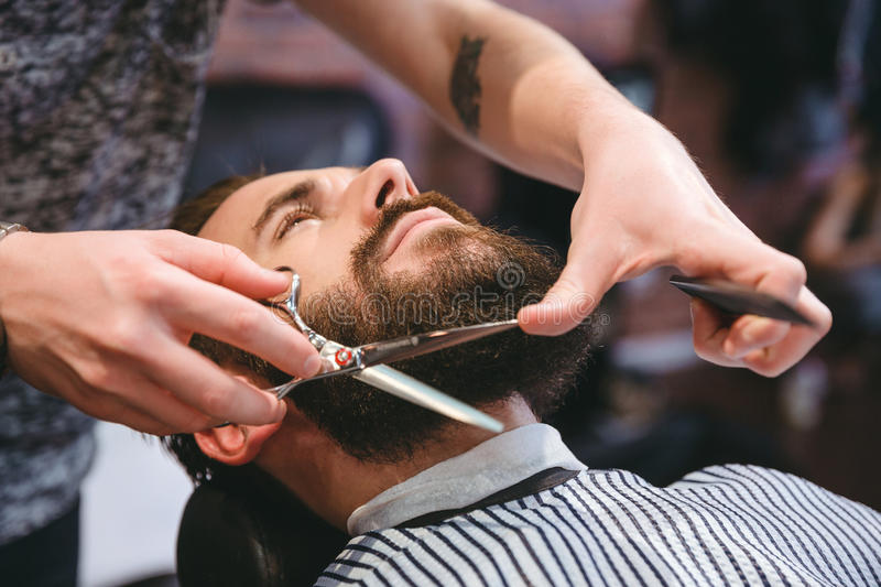 Hairdresser doing haircut of beard to young attractive man stock image