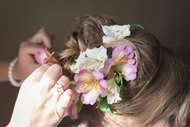 Hairdresser doing a wedding hairstyle with fresh flowers royalty free stock photo