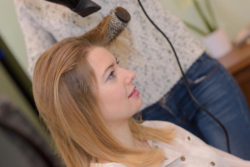 Hairdresser drying clients hair and using round brush stock image