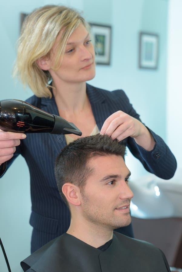 Hairdresser drying hair man stock images