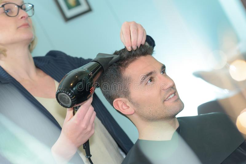 Hairdresser drying man`s hair stock photography