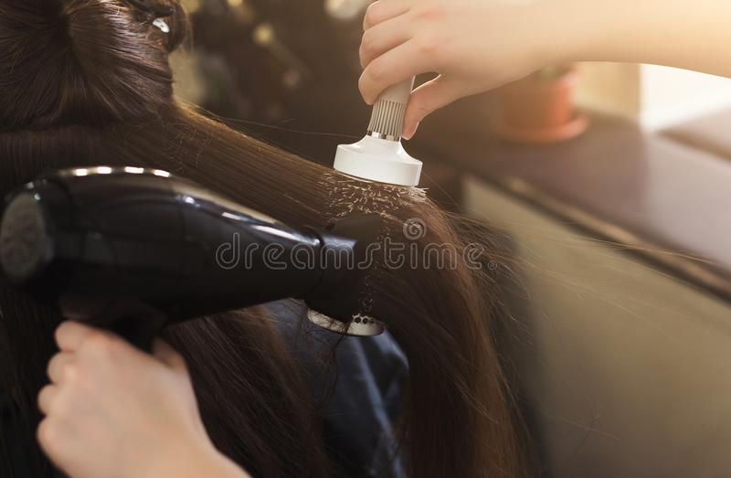 Hairdresser drying woman`s hair in beauty salon stock photography