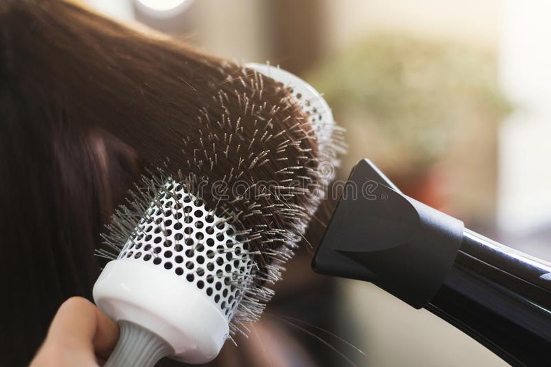 Hairdresser drying woman`s hair in beauty salon. Hairdresser drying woman`s hair with hair dryer and round brush in beauty salon, closeup stock photo