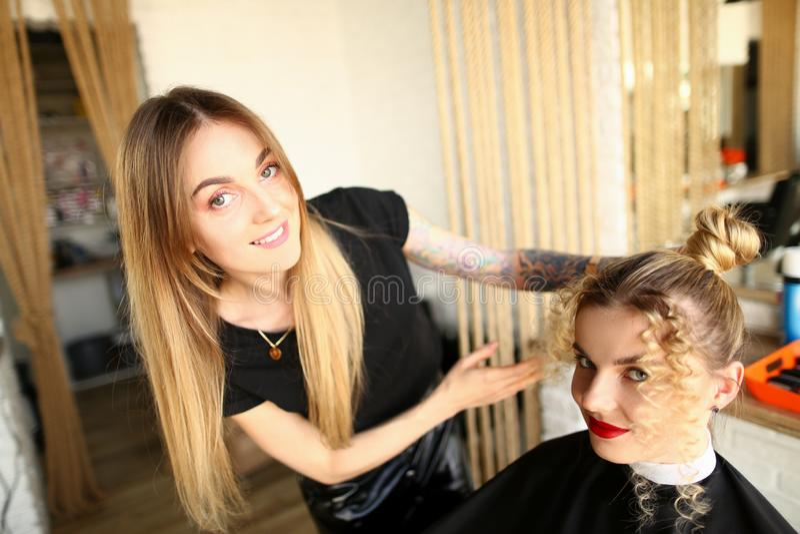 Hairdresser Estimulando Curvões e Bun Girl Hairstyle fotografia de stock royalty free