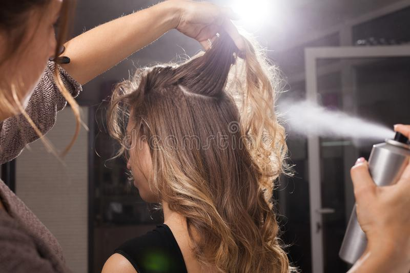 Hairdresser fixing a coiffure of a client with a hair spray. Back view of professional hairdresser fixing a coiffure with curls of a young client using a hair royalty free stock photo