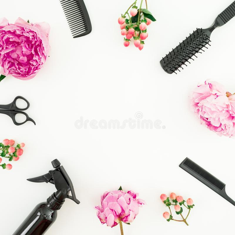 Hairdresser frame concept with spray, scissors, combs and peonies flowers on white background. Flat lay, top view stock photography