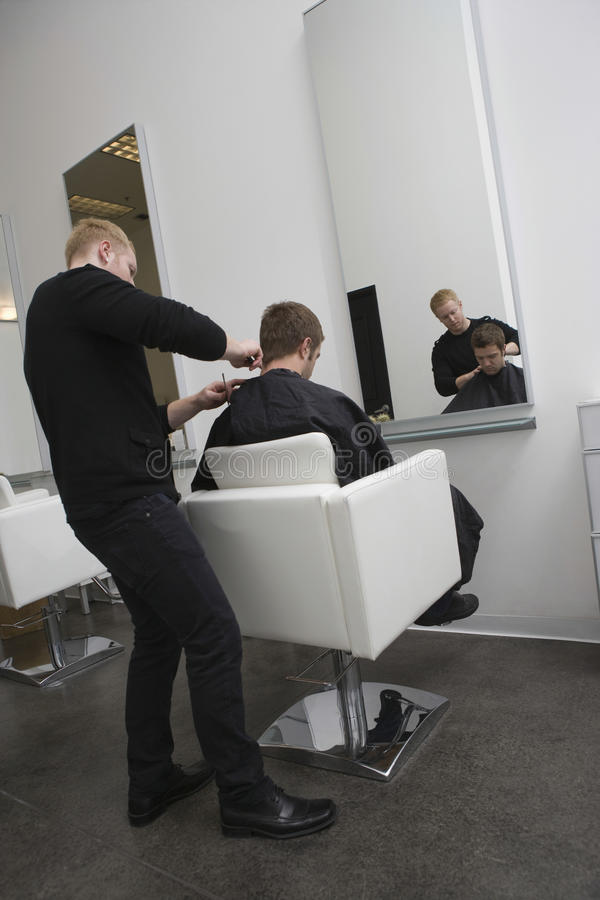 Hairdresser Giving Haircut To Client royalty free stock images
