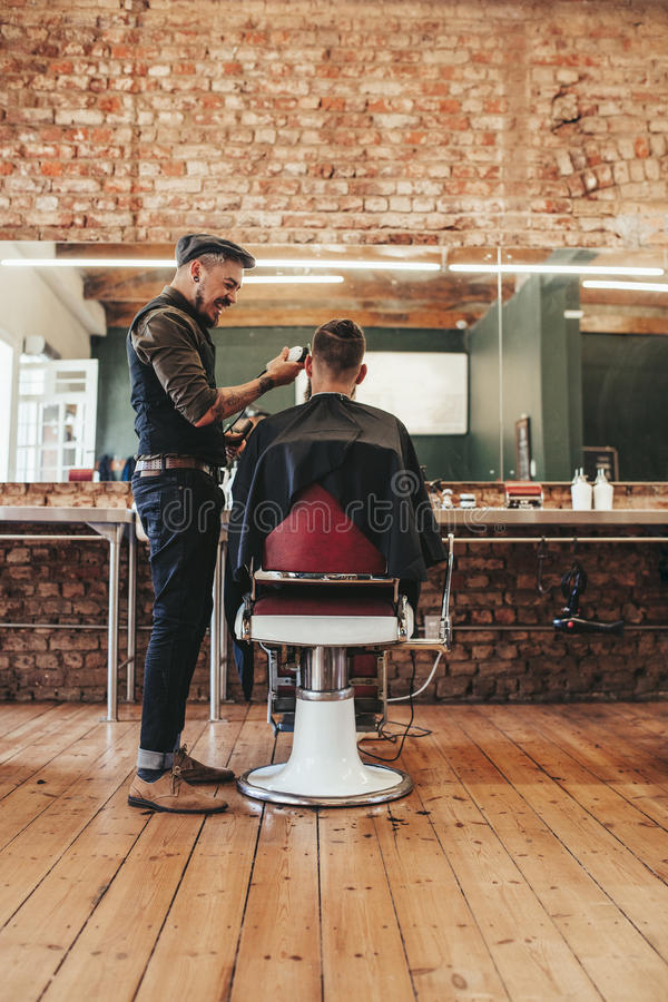 Hairdresser giving haircut to client at salon royalty free stock image