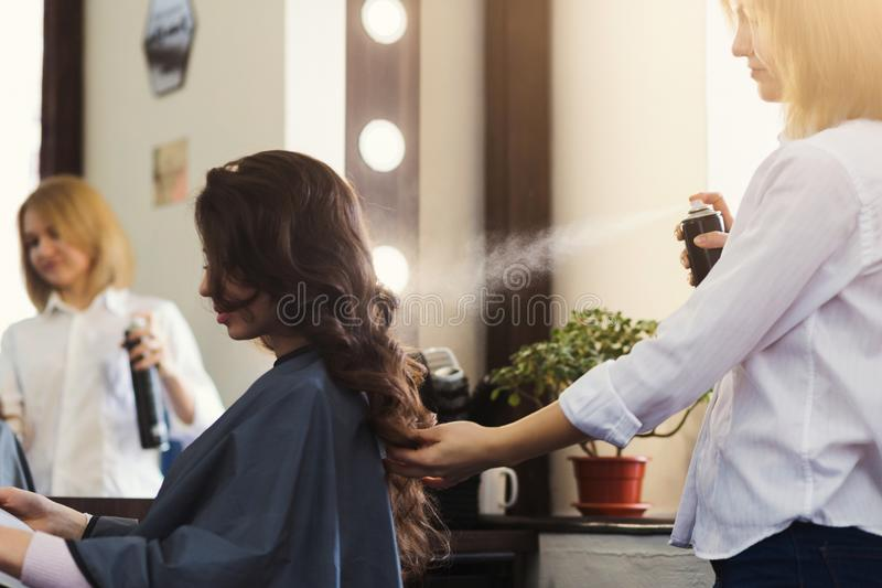 Hairdresser making curly hairstyle at beauty salon. Hairdresser with hair spray making curly hairstyle at beauty salon stock images