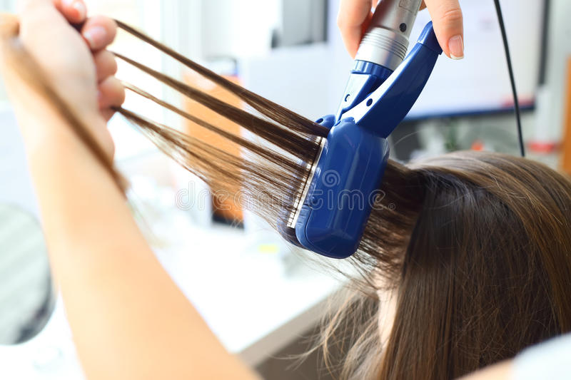 Hairdresser hairstyle models using the straightener . stock images