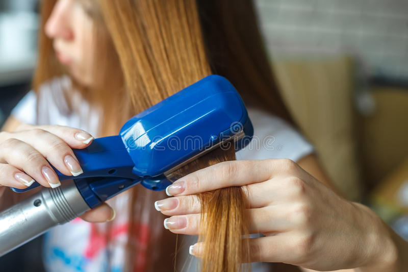Hairdresser hairstyle models using the straightener. Closeup. Selective focus. royalty free stock photography