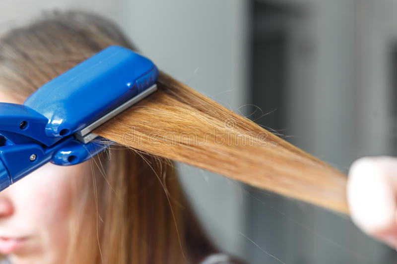 Hairdresser hairstyle models using the straightener. Closeup. Selective focus. royalty free stock image