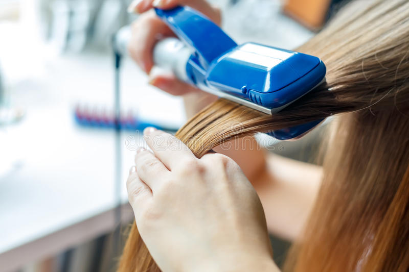 Hairdresser hairstyle models using the straightener. Closeup. Selective focus. royalty free stock photos