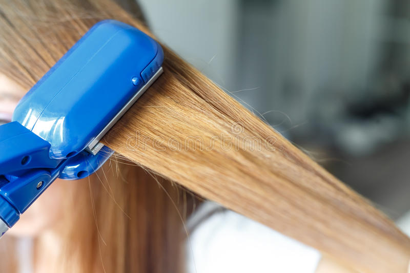 Hairdresser hairstyle models using the straightener. Closeup. Selective focus. royalty free stock photo