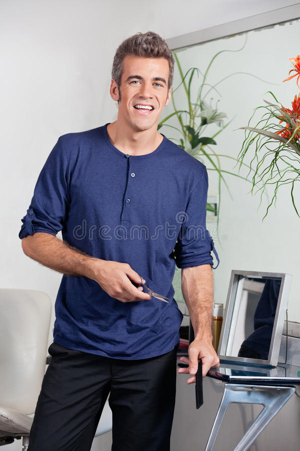 Download Hairdresser Holding Scissors And Comb In Salon Stock Photos - Image: 36989323