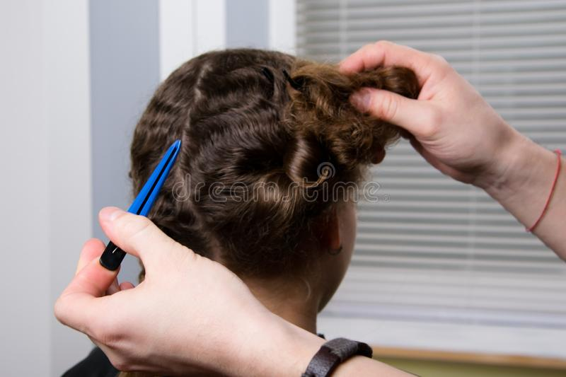 The hairdresser holds a hair clip in his hand and makes a hairdo for the child stock photos