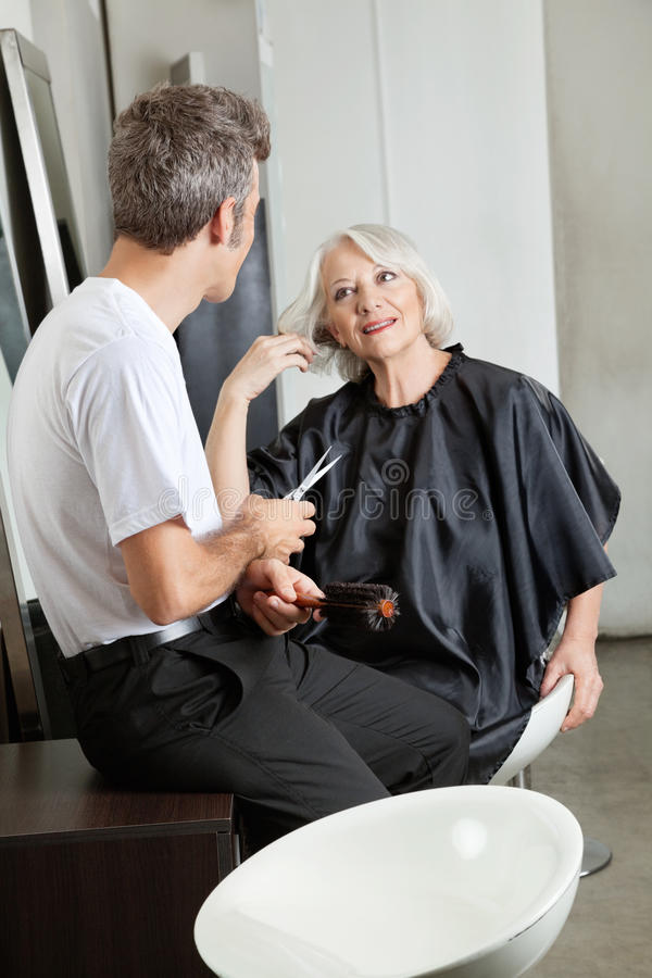 Hairdresser Listening To Female Client. Male hairdresser listening to female client at beauty salon royalty free stock images