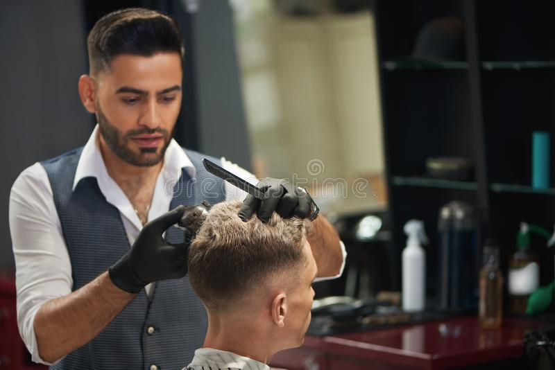 Hairdresser looking at client and trimming his haircut. royalty free stock images