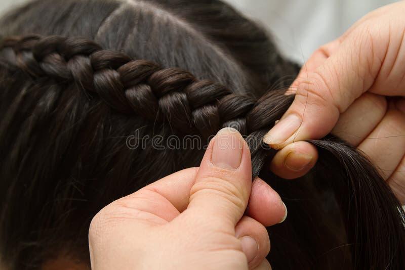 Hairdresser make braids. In beauty salon royalty free stock image