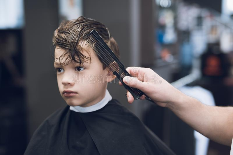 The hairdresser makes a fashionable pretty hairstyle for the boy in a modern barbershop. stock image