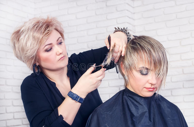 Hairdresser makes a hair cut with scissors royalty free stock photography