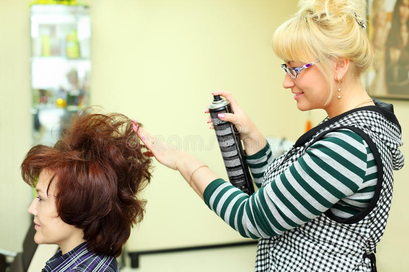 Hairdresser makes hair styling by hair spray. Hairdresser makes hair styling for women by hair spray in beauty salon; focus on hairdo stock images