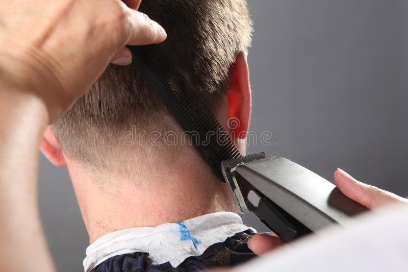 Hairdresser makes hairstyle a man stock photos