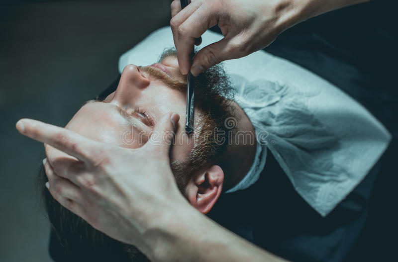 A hairdresser makes a man a haircut of his beard stock images