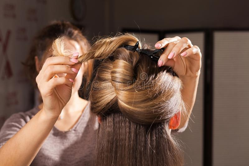 Hairdresser making a coiffure with topknot to a model. Professional hairdresser making an unusual coiffure with a topknot to a brown haired young model in a royalty free stock images