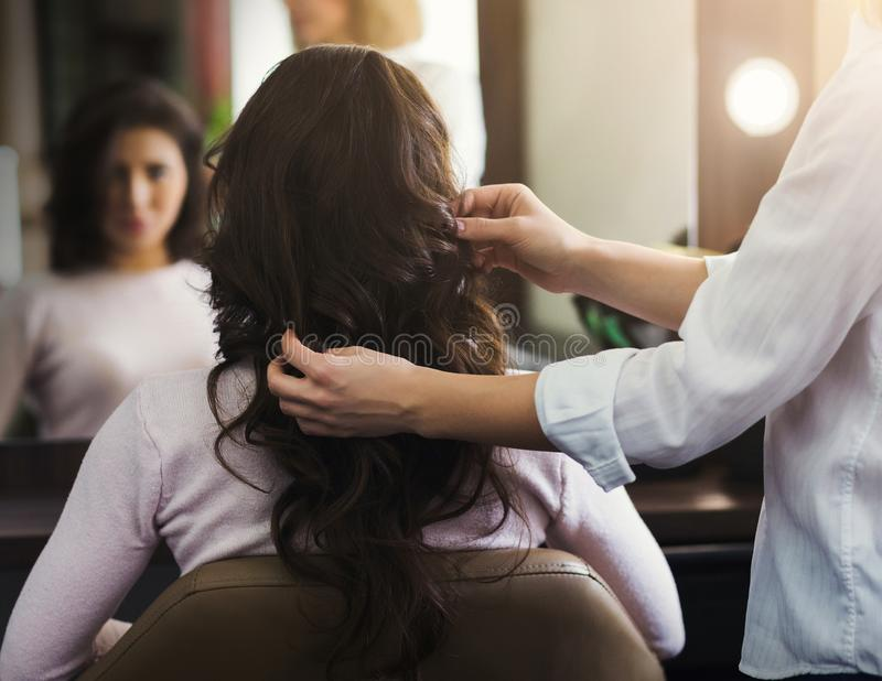 Hairdresser making curly hair to woman royalty free stock image